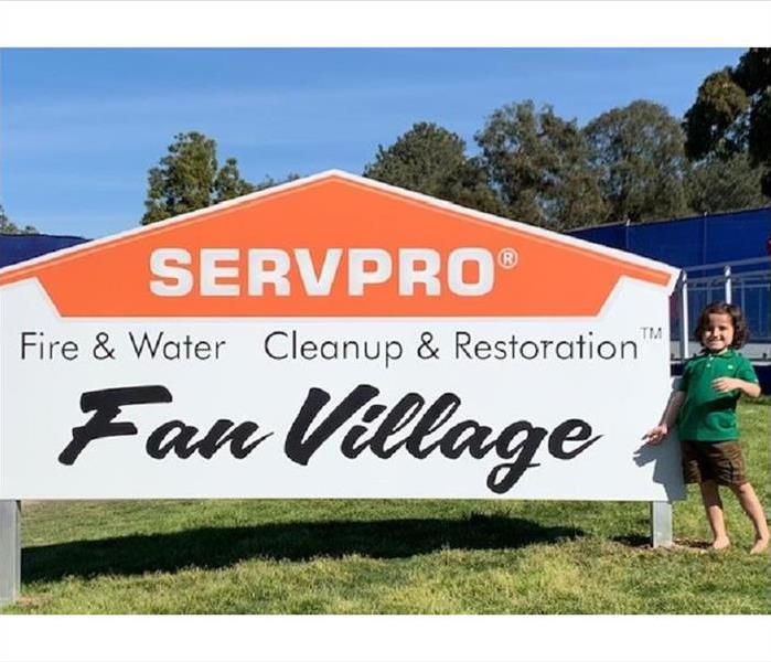 5 year old boy standing in front of a SERVPRO branded sign